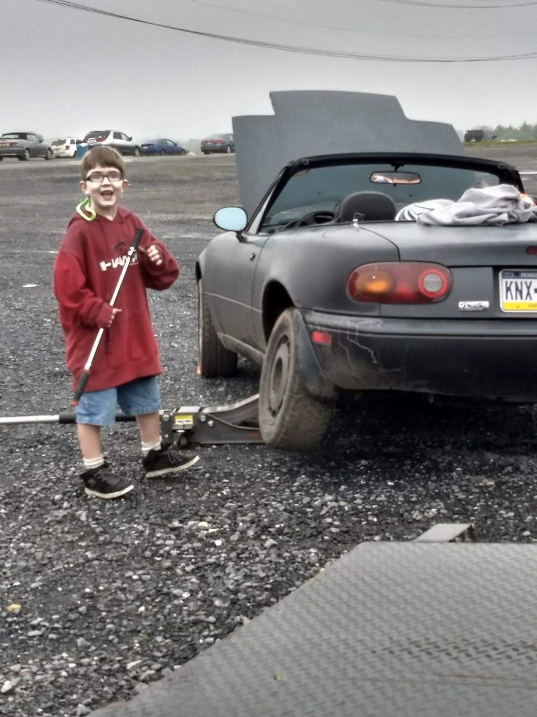 My brother James, helping me swap on some junk tires for drifting.